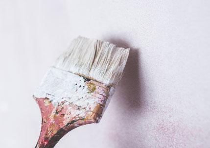 Weiße Wand mit Pinsel mit weißer Farbe, der zum Anstrich ansetzt.