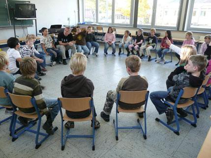 Pit Budde macht mit einer Klasse erst ein paar musikalische Übungen, um dann später das jeweilige KLassenlied einzuüben.