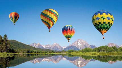 Bunte Fesselballons vor sich in einem See wiederspiegelnden Alpenpanorama