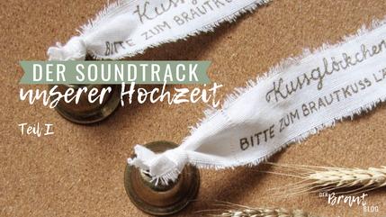 """Zwei Kussglöckchen haben Fähnchen mit der Aufschrift """"Bitte zum Brautkuss läuten."""" Weiterer Text: Der Soundtrack unserer Hochzeit - Teil 1."""
