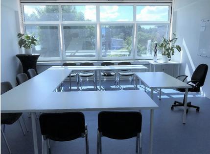 Kursraum für bis zu 15 Teilnehmer/innen mit blauem Fußboden, weißen Doppeltischen und Stühlen.  Links und rechts steht eine grüne Pflanze vor dem Fenster zur Straße