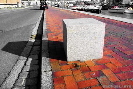 Der Felgenstein ist eine Bremse gegen den Radtourismus in der attraktiven Hafengegend. Als Natursteinwürfel liegt er wirkungsvoll auf dem Fahrradweg und symbolisiert auf abstrakte Weise die Weltkulturerbse.