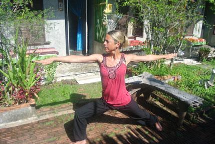 Yogatherapie: Yoga Übungen werden ganz exakt ausgefüht, so wie der Krieger. Frau übt den Krieger in schönem Garten.