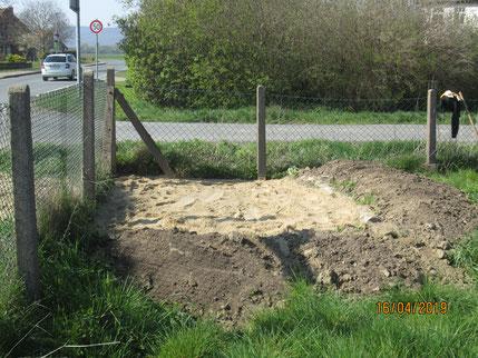 Begrenzungszaun vom Grundstück, davor eine Fläche mit Sand und Erdwall darum