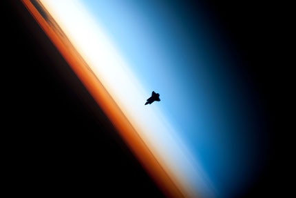 Space Shuttle Endeavour silhouetted against the atmosphere. The orange layer is the troposphere. The shuttle is actually orbiting at an altitude of more than 320 km. By NASA/Crew of Expedition 22, via Wikimedia Commons