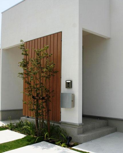白い家のデザインにあわせた四角いポストと表札