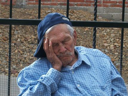Alter Mann mit Basecap schläft auf seine Hand gestützt