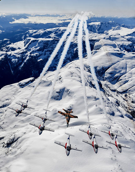 Snowbirds in tight formation low over snow covered mountains.