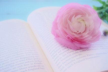 ユリが活けられた白い花びん。ページが広げられた布張りのノートと万年筆。