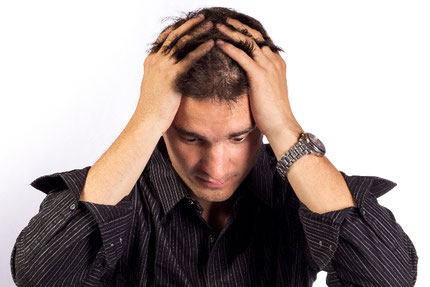 頭をかかえ苦しむ外人男性