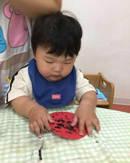 今日は雨だったので、お部屋で遊びました。そらぐみさんは、指スタンプをしました。初めての指スタンプ、絵具の感触はどうだったかな?赤色の画用紙に黒色の絵具、何に変身するか楽しみにしていてくださいね。
