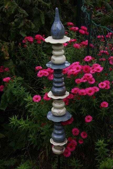 Beige-blaue Keramikstele vor pinkfarbenen Blumen