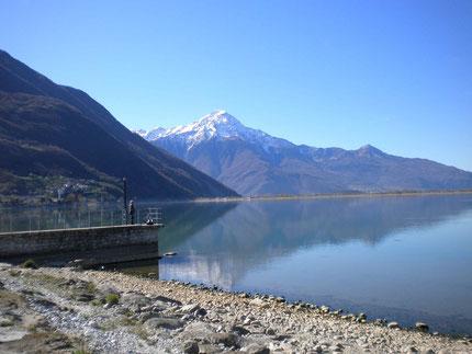 Blick vom Lago di Mezzola in die schneebedeckten Berge