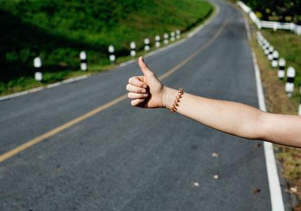 Tramperin am Straßenrand hält ihren Arm raus