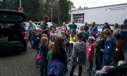 Gruppe von Kindern und Eltern auf einem Parkplatz