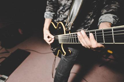 Ein Mann nimmt Gitarrenunterricht in München Schwabing