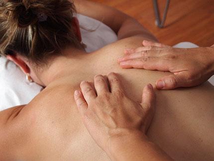 Eine Frau massiert einer anderen Frau den Rücken (Foto).