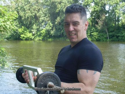 Personal -Trainer Bodymaker Bizepscurl mit Hantel am See