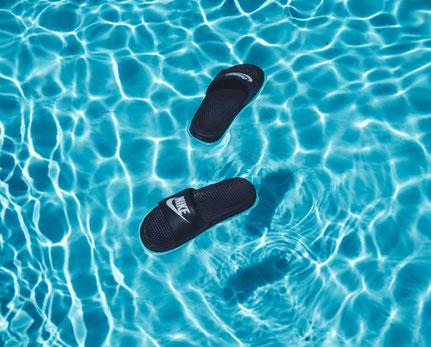 Auf der Wasseroberfläche eines Pools treiben schwarze Badeschlappen.