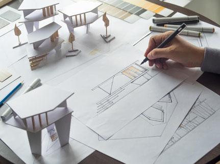 Architekt mit Bauplänen bei der Planung einer Immobilie