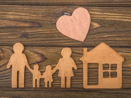 Aus Holz gelegte Familie mit Haus