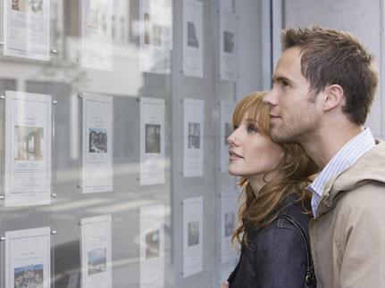 Junges Paar vor Immobilienanzeigen beim Immobilienkauf