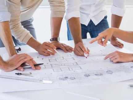 Team von Immobilienfachleuten mit Bauplänen beim Projektmanagement