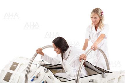 Operator hilft Frau beim Einstieg in die Druckkammer