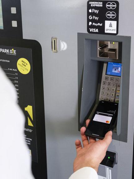 Kunde bezahlt mit Smartphone kontaktlos am Kassenautomaten
