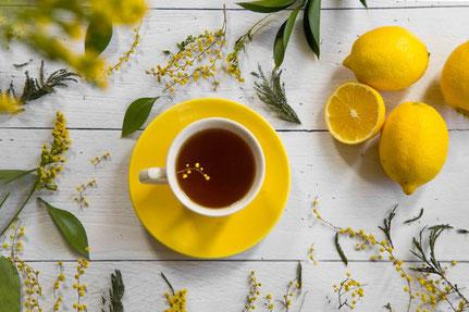 カーネーションとデイジーが活けられた小さな花びん。チョコチップクッキーとコーヒーの入ったマグカップ。
