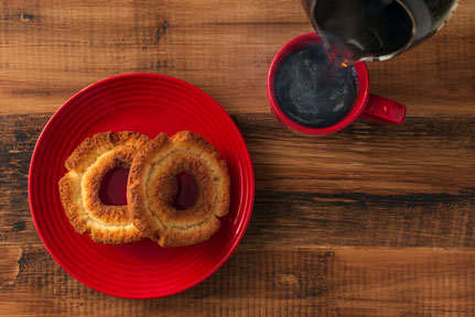 お皿に盛りつけられたドーナッツ3種。ブラックコーヒーのマグ。ほっとひとやすみ。