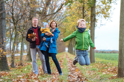 kind-springt-froehlich-hoch-familienshooting-familienfotos-kinderfotos-herbst-duesseldorf-duisburg
