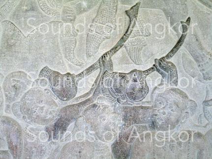 Trompe incurvée en métal (?). On remarquera l'embouchure circulaire. Angkor Vat, Combat des Devas et des Asuras. XIIe s.