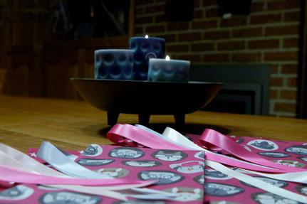 """Pochettes S et M cousues dans le tissu """"têtes animaux sur fond rose"""", avec une bougie en fond."""