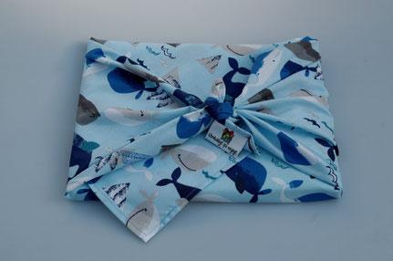 """Livre emballé dans un furoshiki taille M dans le motif """"baleines""""."""
