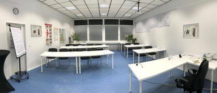 Kursraum für bis zu 2o Teilnehmer/innen mit blauem Fußboden, weißen Doppeltischen und Stühlen.