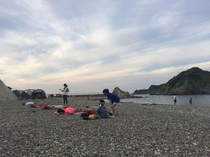 5人ほどのビーチヨガ参加者がビーチに寝転がっています。奥には海で遊ぶ人たちや、複数のテントが。