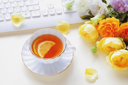 パソコンのキーボード。レモンの輪切りが浮かんだ紅茶のカップ。バラのブーケ。