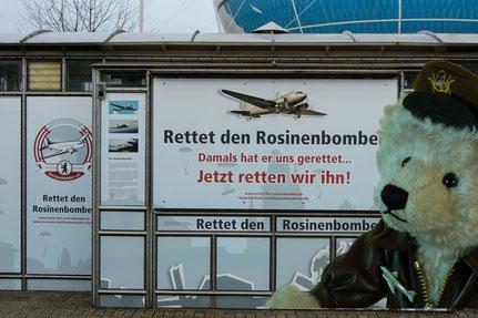 © Dr. Ursula Fellberg, Rosinenbomber Teddy vor dem Plakat des Fördervereins  am  Checkpoint Charly in Berlin, aufgenommen 2013