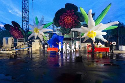 Riesige aufblasbare Blumen erscheinen als Showeffekt auf der Bühne.