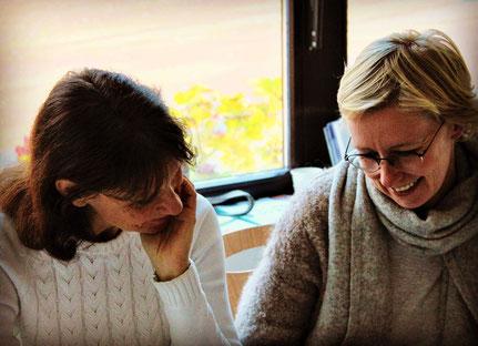 Anja Orywol und Steffi Eikel bei der Arbeit vor einem Fenster mit gesenktem Blick zum Thema Essstörungen in der traditionellen chinesischen Medizin 5 Elemente Ernährung Seminar