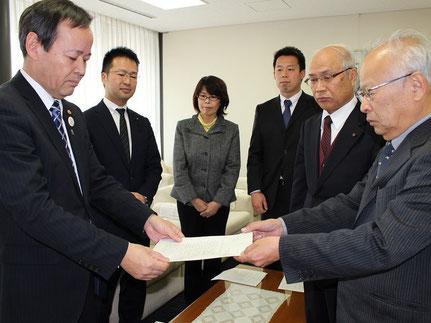 申し入れ書を手渡す小村吉一党市委員長(右)