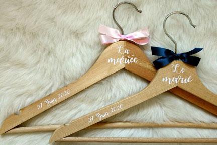 cette photo représente des cintres personnalisés pour un mariage, en bois avec stickers blancs