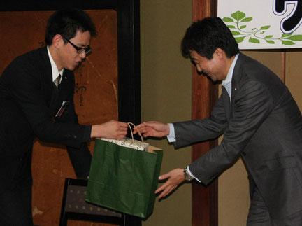 謝辞を述べ、岡西副知事に記念品を手渡す、綾部青年会議所の岡田太郎副理事長