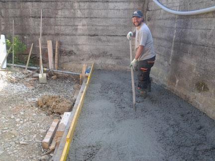 Fabian beim Einbringen eines Betonbodens.