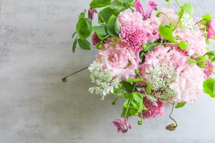 パソコンのキーボードの前に置かれた手紙の入った封筒とボールペン。オレンジピンクのバラとガーベラの花。