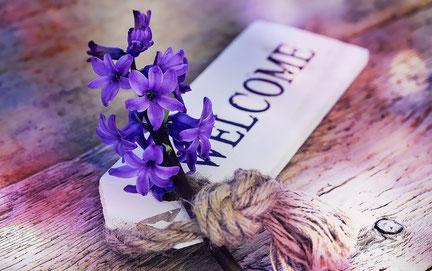 """Hyazinthe auf Schild """"Willkommen"""": Begleiten Sie die Wiederöffnung mit Ihrer Kommunikation"""