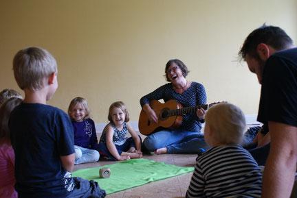 Raphaela Merz sitzt lachend und Gitarre spielend mit kleinen Kindern auf dem Boden um eine grüne Decke herum und singt mit ihnen.