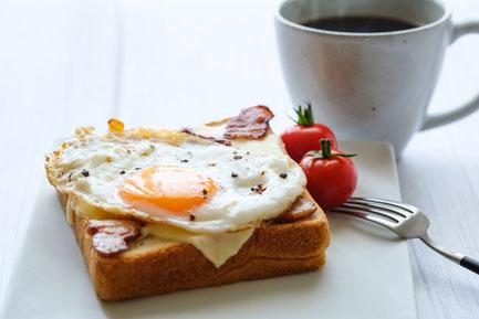 カフェのモーニングセット。目玉焼きとベーコンがのったトーストとミニトマトのプレート。ホットコーヒー。