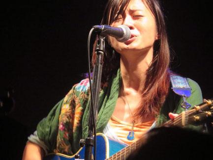シンガーソングライターの詠美衣が泣きながらギターの弾き語りをしている場面